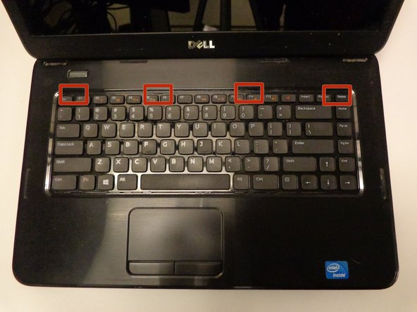 Image 1/2: Using the spudger, push the tabs away from the keyboard and pull the keyboard up away from the laptop.