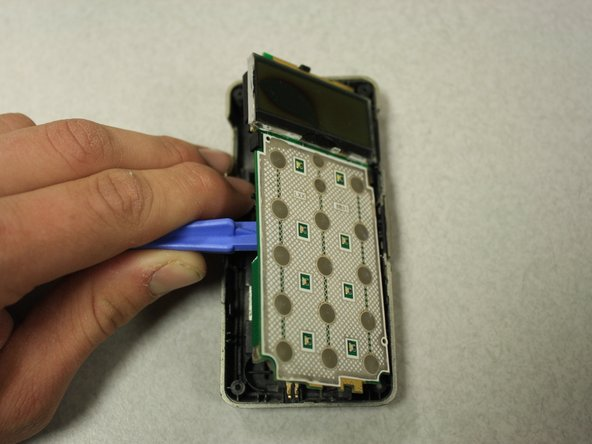 Use the opening tools to seperate the circuit board from inside of the back case by prying between the circuit board and the case as shown.