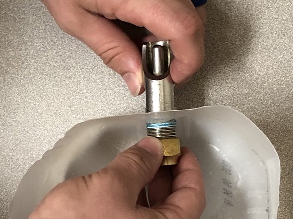 With an adjustable wrench, unscrew the nut on the inside located near the base on the backside of the nipple.