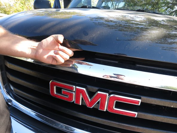 You will find this release latch near the center of the hood in the small gap between the hood and grille.