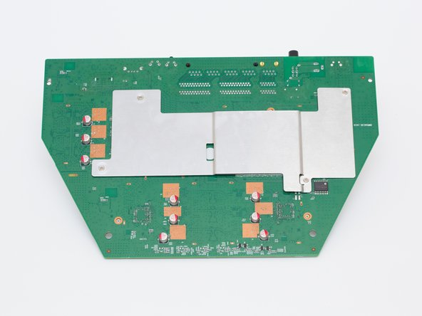 Image 2/3: Locate the reset switch's 4 solder joints on the underside of the motherboard.