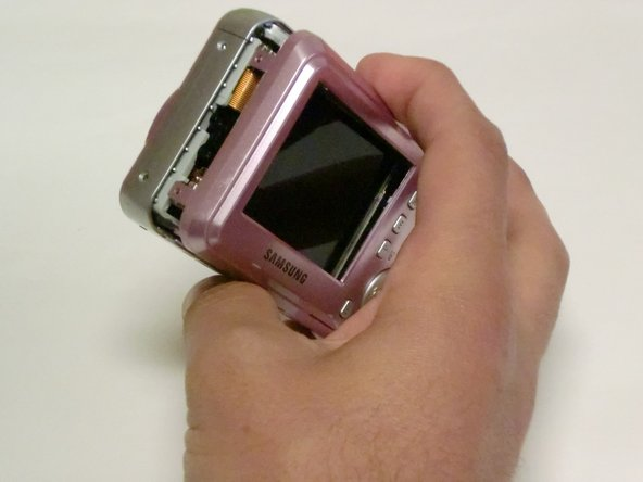 Carefully pull the back of the camera (the LCD screen side) away from the front.