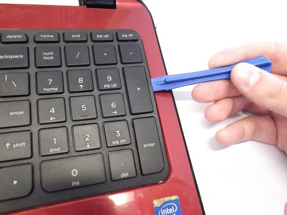 Image 1/3: Use the plastic opening tool to pry the keyboard upwards from the bottom right hand corner of the keyboard.