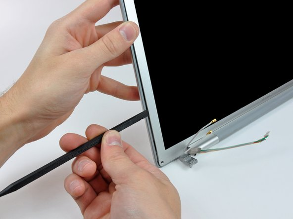 Image 2/3: With the spudger still inserted, rotate it away from the display to separate the front and rear bezels.