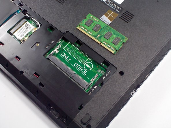Slide the memory module out of its slot and lift it out of the laptop base.