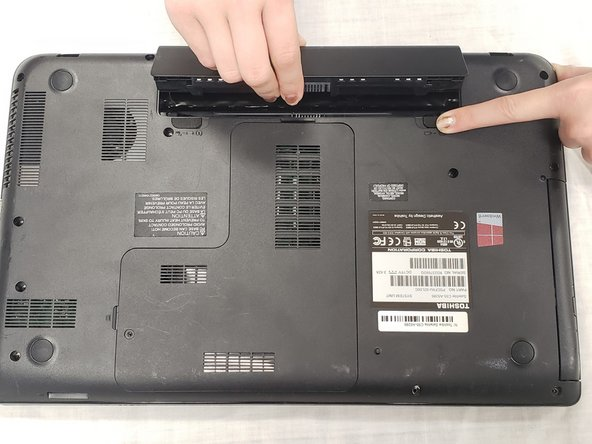 Lifting from the small notch between the two tabs, pull the battery out of the laptop.