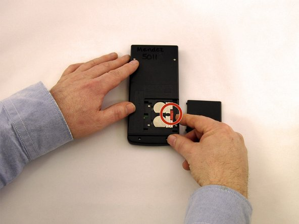 Image 1/3: Slide the metal tab of the top battery to the right.