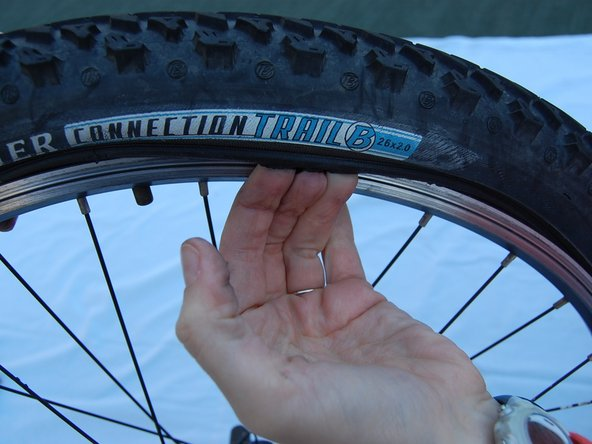 Image 1/2: Slide your fingers (still under the tire coping) around the circumference of the tire until you completely remove the tire from the rim.
