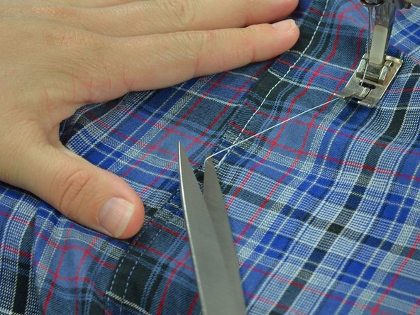 After you've completely sewn over the torn seam, clip the threads and free the garment from the machine.