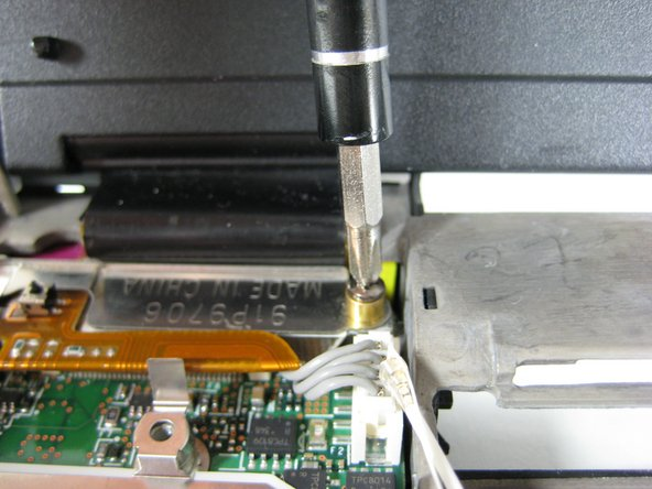 Remove a single screw from the metal plate that secures the display cable.