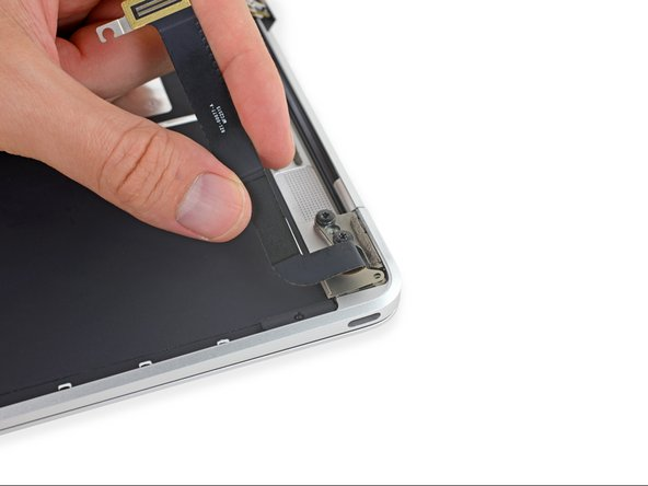 Unfold the USB-C port ribbon cable until it lays flat, allowing access to the bracket beneath.
