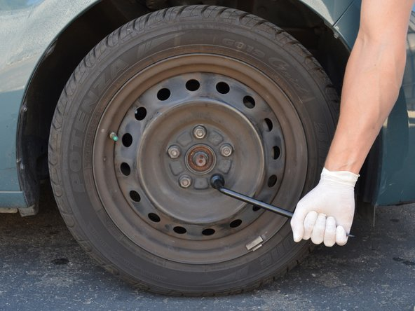 If you have steel wheels with wheel covers, use a large flat head screwdriver or the tip of the emergency tire iron to pry off the wheel cover to access the lug nuts.