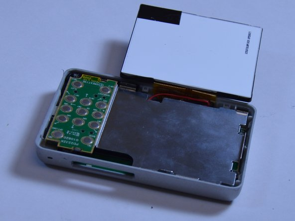 Flip the LCD screen off the midsection plate to gain access to the space around the input button chip.
