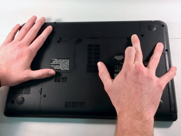 Press down with your fingers while also applying a sliding motion on the latch buttons near the battery on the underside of your laptop.