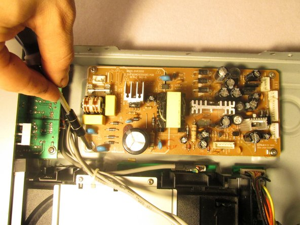 Place the blue plastic tool opener underneath the side of the circuit board and carefully remove it from the DVD player.