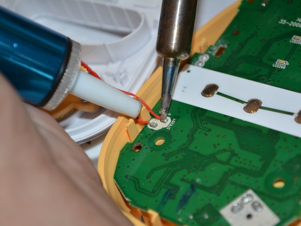 Remove the solder from the bottom left corner of the motherboard to completely detach the speaker from the device.