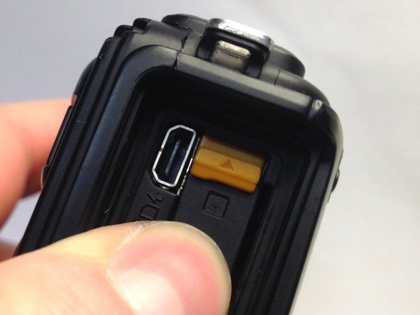 Push the yellow battery/charger compartment tab up using your thumb nail.