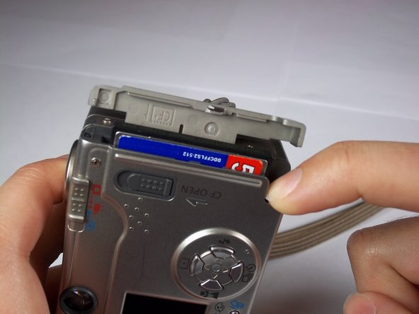 Push down on the black square button next to the memory card slot. This will release the memory card from the slot.
