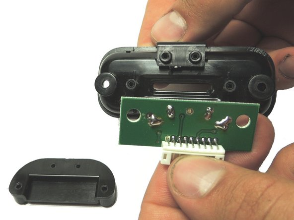 Remove both of the black plastic pieces. They should easily slide off of the two guide holes in the circuit board.