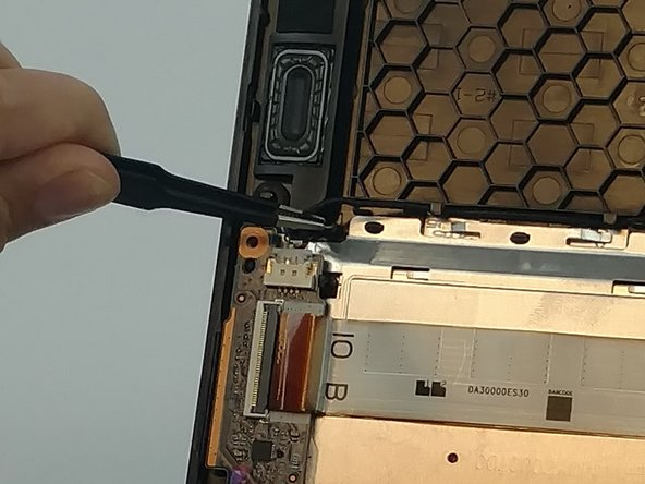 Using a pair of tweezers, dissconnect the speakers on the left side of the laptop.