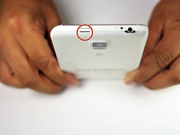 Use your Supdger to remove the back cover of the phone using notch located in the top left corner of the phone.
