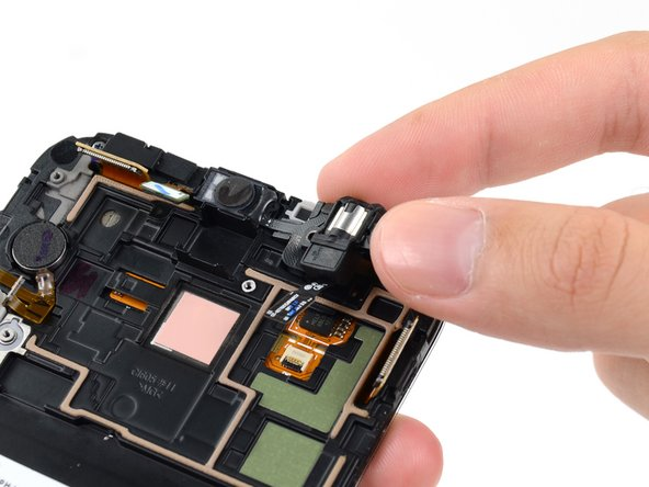 Grasp the headphone jack portion of the assembly and lift it out of its groove in the display assembly.