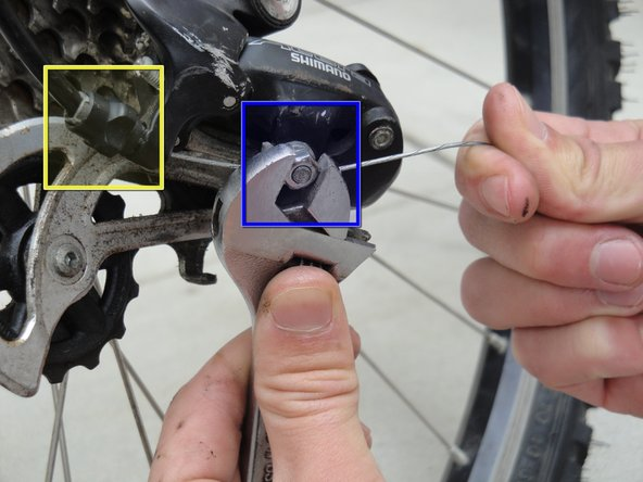 Image 2/2: Pull the slack out of the cable while clamping it down with the nut that is attached to the derailleur.
