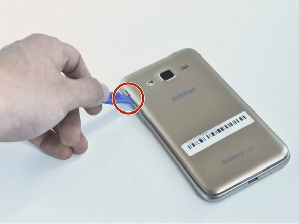 Remove the back case of the phone by using an opening tool or fingernail to lift the divot on the top left side.