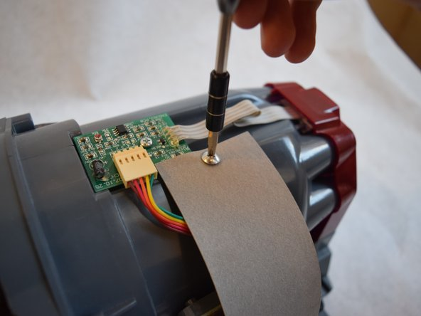 """Remove both 3/8"""" Ph2 screws attached to the grey belt at the top and bottom."""