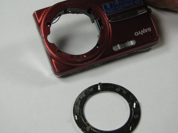 Remove round silver bezel from the front of the camera.