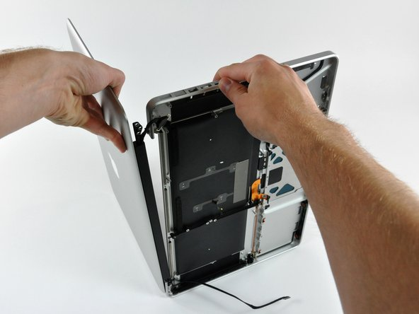 Image 3/3: Lift the display away from the upper case, minding any brackets or cables that may get caught.