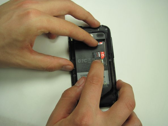 Image 1/2: While keeping pressure on the clip, use another finger to gently slide the SIM card down over the clip.