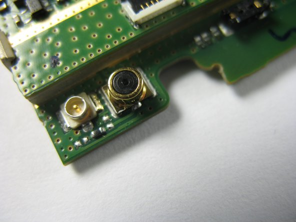 Unsolder the microphone located at the top right corner of the motherboard near the silver jack.