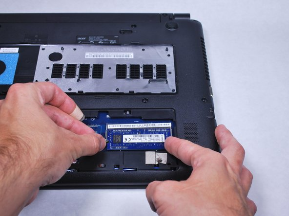 Use your fingers to pinch the retaining latch. This will free the RAM.