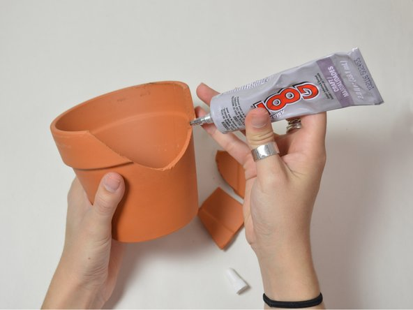 Apply craft adhesive along the broken portion of the pot.