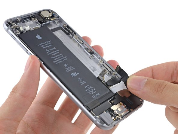 Continue pulling the adhesive tab upward and away from the right edge of the battery, allowing it to slowly slide out from between the battery and the rear case, until the strip comes free from the iPhone.