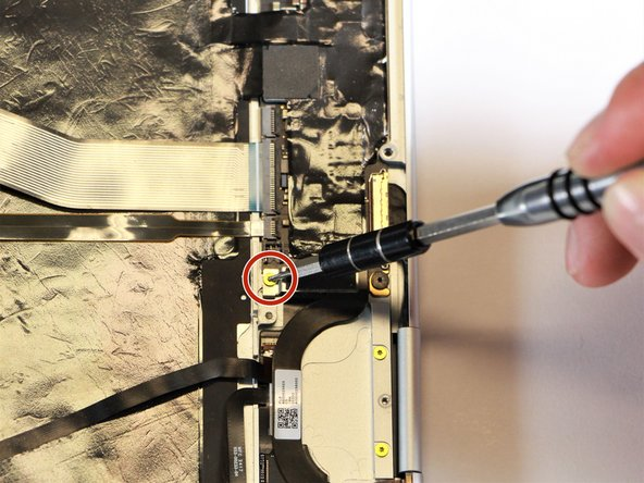Remove the gold 2.0mm corner screw by turning it counterclockwise with a T3 Torx screwdriver.
