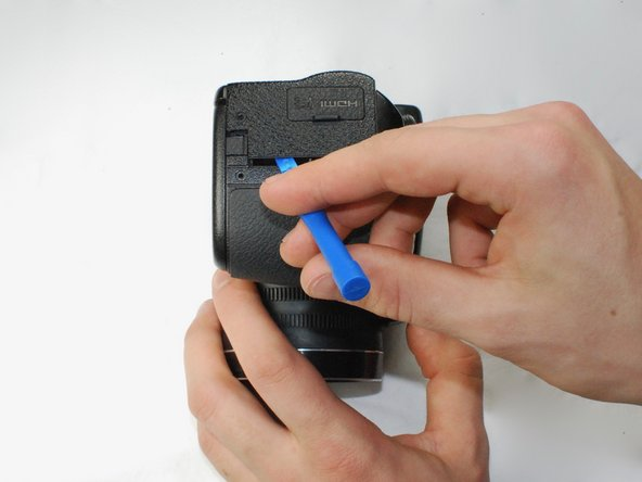 Use a plastic opening tool to separate the back panel from the camera on the left side, then remove the back panel from the camera.