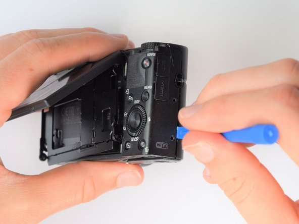 Using the same plastic opening tools, separate the screen and back assembly from the front portion of the camera