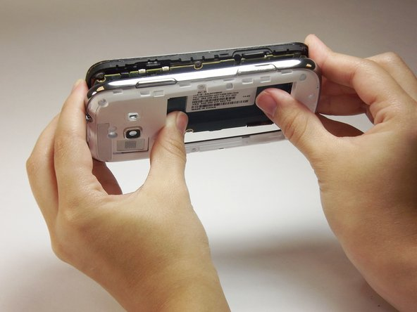 Use your thumbs to separate the motherboard from the back of the phone.