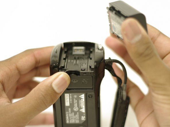 Using your right index finger and thumb, pull the battery toward you and then away from the camera.