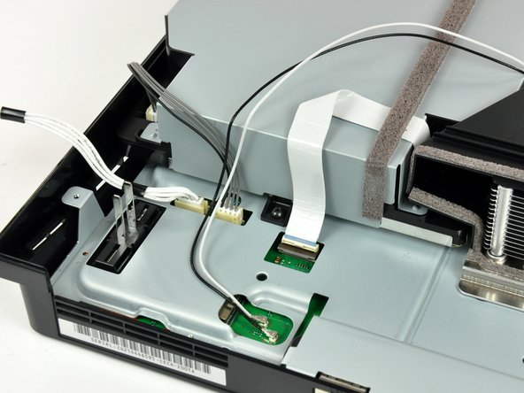 If present, remove the pieces of tape securing the cables to the body of the Blu-ray drive.
