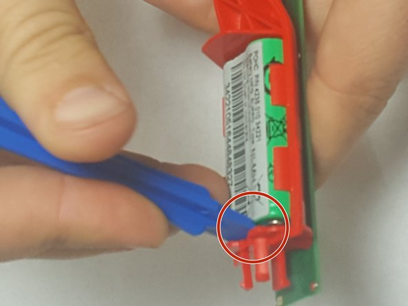 Pry the battery out of the side closest to the charging coil as shown in the photo by the red circle.