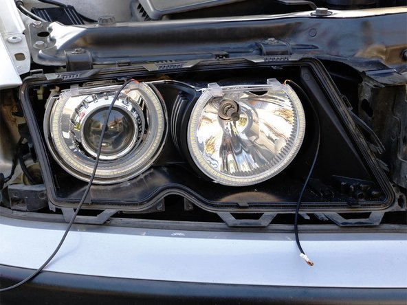 Clip on the switchback LED angel eye rings. Grab the two black wires through the low beam bulb back openings.
