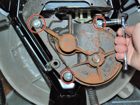 On the bottom of the machine, remove the 3 bolts that hold the transmission in place with the ratchet and a 3/8 inch socket.