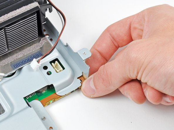 Image 1/2: Gently press the board away from the top shield assembly near the fan connector and the corner of the board near the wireless sockets.