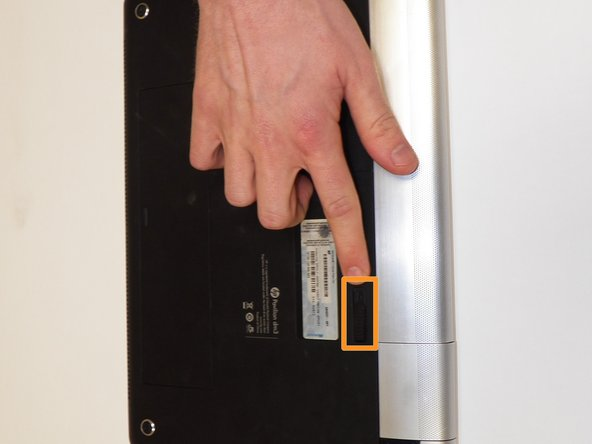 Flip laptop to bottom side and locate the battery eject switch.