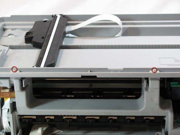 Image 2/2: Remove the two T10 12 mm Torx screws from the top front of the printer