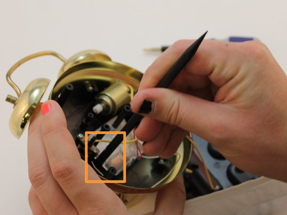 Insert the flat end of a spudger on both sides of the wiring box to open and detach the box from the clock.