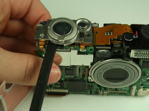 Using a spudger, carefully pry the shutter button assembly from the camera.